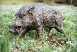 A patinated bronze model of a walking boar