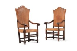 A pair of Italian walnut and leather upholstered armchairs