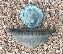 A verdigris bronze lion mask wall fount