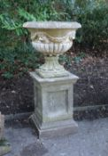 A stone composition urn on plinth