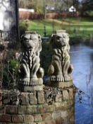 A pair of stone composition heraldic finials modelled as lions sejant