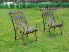 A pair of wrought iron garden armchairs