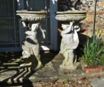 A pair of stone composition figural planters or bird baths