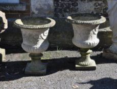 A pair of small-scale stone composition garden vases