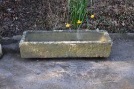 A carved sandstone or limestone garden trough or basin