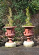 A pair of red painted cast iron models of the Borghese vase