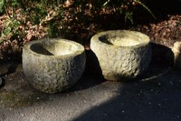 A pair of rough-hewn stone planters