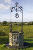 A Continental sculpted limestone and wrought iron mounted well head