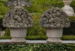 A pair of large Continental carved limestone baskets of flowers and fruit in 18th century style