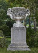 A stone composition twin handled garden urn on plinth