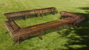 A set of five wrought iron garden benches constituting an open rectangular formation