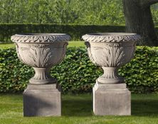 A pair of substantial carved limestone urns on plinths