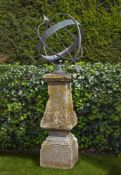 A patinated bronze mounted carved limestone armillary sphere