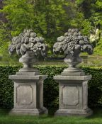 A pair of sculpted limestone pier finials modelled as vases of fruit