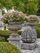 A pair of continental carved limestone garden urns on plinths