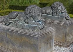 A pair of patinated bronze models of recumbent lions