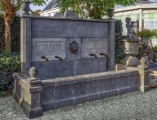 A monumental carved stone wall fountain