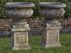 A pair of Continental carved limestone urns on plinths
