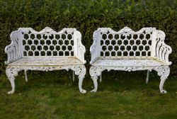 A pair of white painted cast iron garden seats