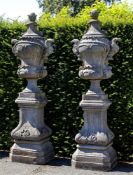 A pair of carved limestone garden urns on plinths