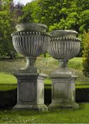 A pair of large and impressive Italian carved limestone garden urns on plinths in Impero taste
