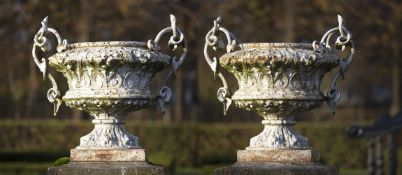 A large pair of French white painted cast iron twin handled urns
