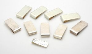 A collection of silver hammered rectangular money clips