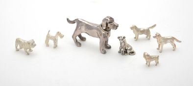 A collection of silver and silver coloured models of dogs