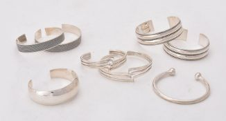 A collection of silver and silver coloured bangles