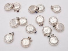 A collection of silver circular scent bottles