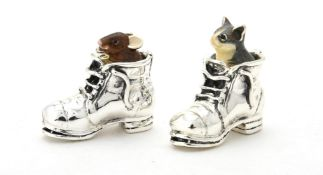 A silver and enamel model of a mouse and a cat in a boot