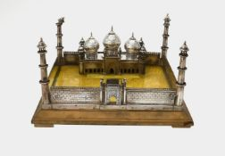 An unmarked silver coloured model of a mosque