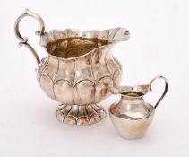 A continental silver coloured lobed cream jug