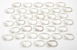 A collection of silver coloured oval clips