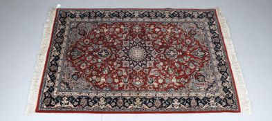 A Nain style rug with claret red field with central medallion surrounded by birds and foliage