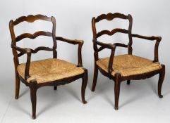 A pair of late 19th century French oak armchairs