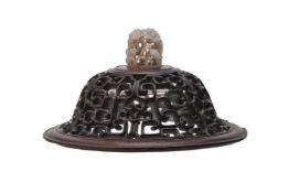 A Chinese carved hardwood cover with jade finial