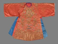A Chinese coral ground child's silk dragon robe