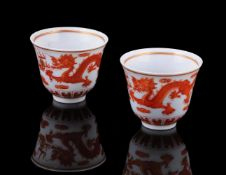 A pair of Chinese iron red 'Dragon and phoenix' wine cups