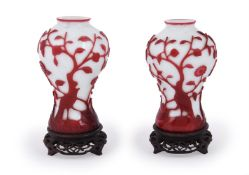 A pair of Chinese red overlay white Peking glass 'Bird and Peach Tree' vases