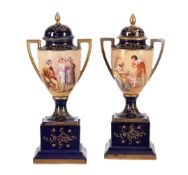 A pair of Vienna-style blue-ground and gilt urns and covers on plinth bases
