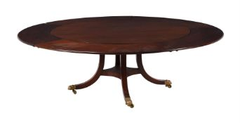 A mahogany circular extending dining table with five detachable leaves