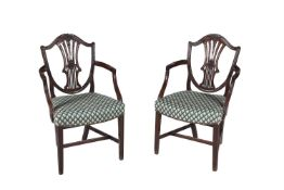 A pair of George III mahogany shield back elbow chairs