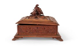 A 'BLACK FOREST' CARVED AND STAINED WOOD CASKET