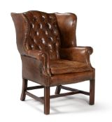 A MAHOGANY AND LEATHER UPHOLSTERED WING ARMCHAIR, 20TH CENTURY