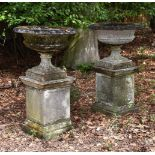 A PAIR OF COMPOSITION STONE URNS ON PEDESTALS, 20TH CENTURY
