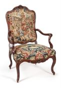 A LOUIS XV CARVED WALNUT AND NEEDLEWORK UPHOLSTERED ARMCHAIR, MID 18TH CENTURY