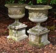 A LARGE PAIR OF COMPOSITION STONE URNS WITH CHERUB RELIEFS, 20TH CENTURY