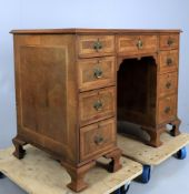 A walnut and featherbanded kneehole desk in the George II style