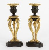 A pair of French Empire parcel gilt and patinated bronze candlesticks